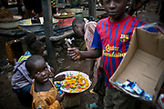 Children sell chili peppers and chewing gum in a market area in Bangui. With the poor economy, few operating schools, and a high illiteracy rate, children are often forced to earn a living through manual labor and street vending.