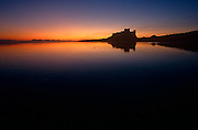 Dawn breaks over the sandy low-tide beach of Northumberland coast and a distant Bamburgh Castle