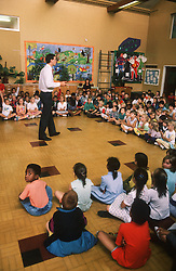 Nursery school assembly with teacher talking to pupils in school hall,