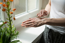 Midsection of a young woman applying cream on her hand, Munich, Bavaria, Germany