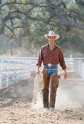 Cowboy holding his lasso walking down a dusty road