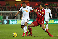 Jordan Ayew of Swansea city is challenged by Virgil van Dijk of Liverpool (r). Premier league match, Swansea city v Liverpool at the Liberty Stadium in Swansea, South Wales on Monday 22nd January 2018. <br /> pic by  Andrew Orchard, Andrew Orchard sports photography.