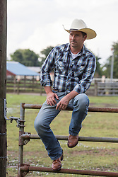 portrait of a handsome cowboy outdoors sitting on a metal gate