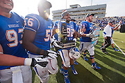 Dec 1, 2012; Tulsa, Ok, USA; Tulsa Hurricanes defensive end Cory Davis (93) defensive tackles Daeshon Bufford (56) Derrick Jackson (92) and offensive tackle Jared Grigg (72) carry a trophy off the field following a game against the University of Central Florida Knights at Skelly Field at H.A. Chapman Stadium. Tulsa defeated UCF 33-27 in overtime to win the CUSA Championship. Mandatory Credit: Beth Hall-USA TODAY Sports