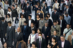 Crowds of  commuters walking to work during morning rush hour in central Tokyo Japan