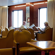 Three weeks aboard the Kong Harald. Hurtigruten, the Coastal Express. Aboard the ship. People reading a book.