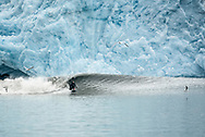 Kyle Hofseth surfs a wave below a glacier in the Gulf of Alaska. As the glacier calves — drops ice into the water — waves form below the icy cliff.