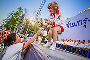 01 MARCH 2013 - BANGKOK, THAILAND: .DARUNEE KRITTABOONYALAI, (right) a Thai Red Shirt activist and supporter of Pheu Thai Gubernatorial candidate Pongsapat Pongchareon, accepts flowers during the last Pheu Thai election campaign of the Governor's race. The election is Sunday, March 3 and no campaigning is allowed 24 hours before election day. Police General Pongsapat Pongcharoen (retired), a former deputy national police chief who also served as secretary-general of the Narcotics Control Board is the Pheu Thai Party candidate in the upcoming Bangkok governor's election. He resigned from the police force to run for Governor. Former Prime Minister Thaksin Shinawatra reportedly personally recruited Pongsapat. Most of Thailand's reputable polls have reported that Pongsapat is leading in the race and likely to defeat Sukhumbhand Paribatra, the Thai Democrats' candidate and incumbent. The loss of Bangkok would be a serious blow to the Democrats, whose national base has been the Bangkok area.     PHOTO BY JACK KURTZ
