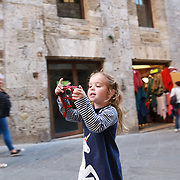 SAN GIMIGNANO, ITALY - OCTOBER 25: A young girl takes a photograph of a street scene in San Gimignano. San Gimignano is an Italian hill town in Tuscany, southwest of Florence. Encircled by 13th-century walls, its old town centers on Piazza della Cisterna, a triangular square lined with medieval houses. It has a skyline of medieval towers, including the stone Torre Grossa. San Gimignano, Tuscany, Italy. 25th October 2017. Photo by Tim Clayton/Corbis via Getty Images)