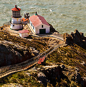 SUBJECT: Lighthouse at Point Reyes. IMAGE: One of the minority, you climb DOWN to this light. Perched on a rocky promentory, the light is shown here with the vigour of rough waves and winds evident.