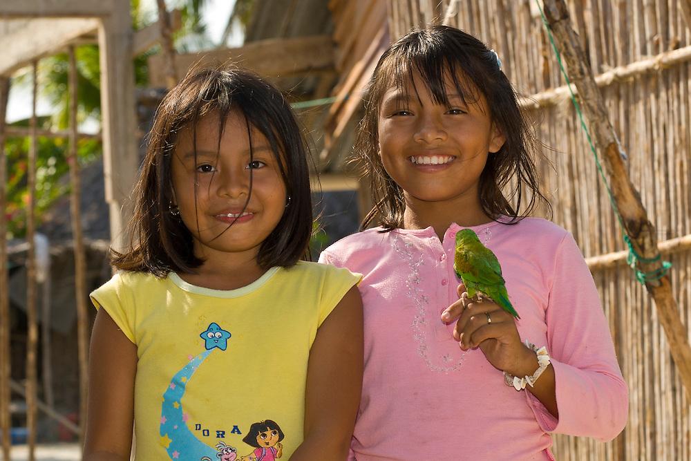Kuna Indian girls holding a parakeet in her village on Corbisky Island, San Blas Islands (Kuna Yala), Caribbean Sea, Panama