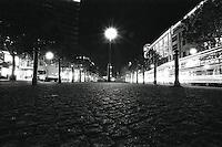 En lyktestolpe lyser opp brosteinen mens biler kjører forbi i gaten på dette nattbildet fra Berlin.<br /> <br /> Berlin street photography 2010. Gatefotografi fra Berlin i 2010.<br /> <br /> Foto: Svein Ove Ekornesvåg