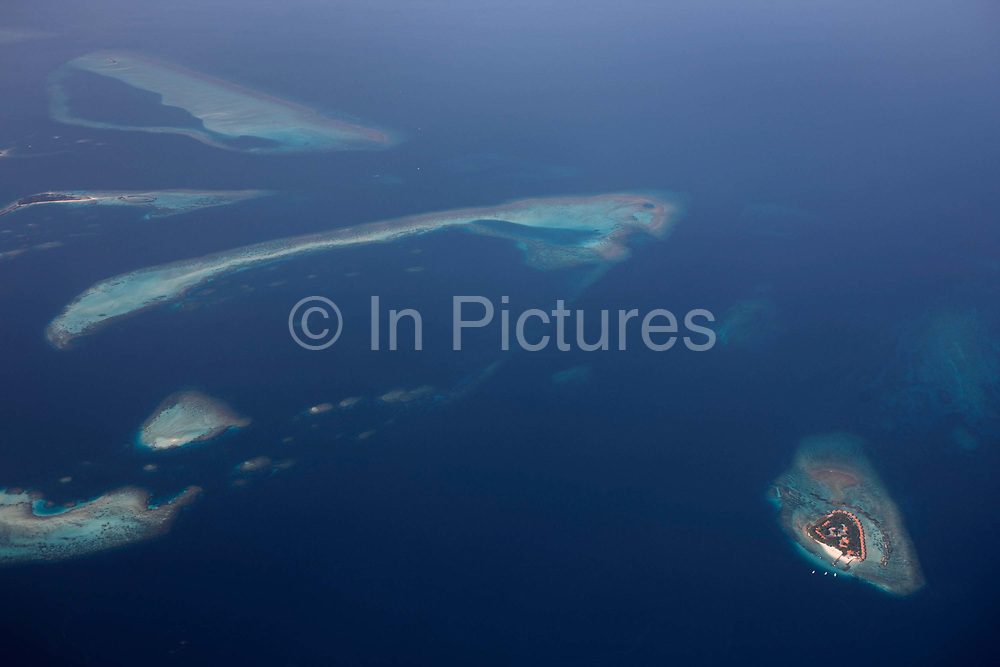 An aerial view of unidentified islands seen from a regional aircraft passing overhead the atolls and islands to the north Malé, capital of the Indian Ocean Republic of the Maldives. We see the perfectly clear blue sea surrounding the islands and tiny sandbanks of white coral beach sand, all of which are in jeopardy of rising sea levels as global warming makes sea level locations like this vulnerable to being overwhelmed. The only sign of life is the tiny island in the bottom right of frame where holiday resort accommodation ring this dot in the ocean. The Maldives comprise of twenty-six atolls, featuring 1,192 coral islands of which 80 are holiday resorts with 200 inhabited by indigenous communities. This Islamic nation of 298 sq km (115 sq miles), lie seven hundred kilometres (435 miles) south-west of Sri Lanka.