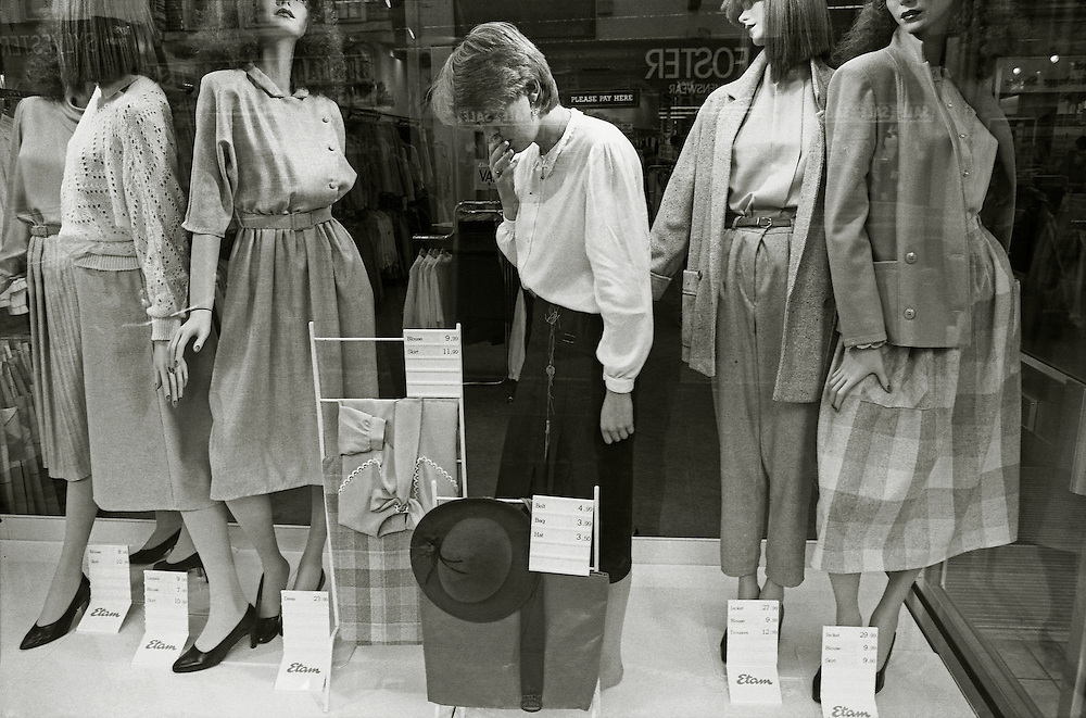 A young woman dresses a window in a clothes shop in England. 1984.