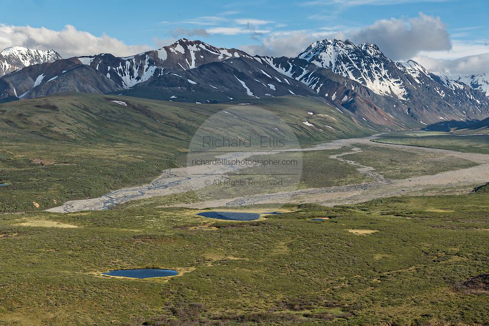 View of the Polychrome Hills and the Alaska Range and the Toklat River in Denali National Park Alaska. Denali National Park and Preserve encompasses 6 million acres of Alaska's interior wilderness.