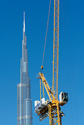 Burj Khalifa and crane at construction site in Dubai United Arab Emirates