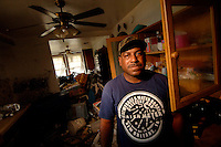 """""""I live here with me, my wife, my 2 daughters, my 2 sons, and 6 grandchildren. I evacuated from Austin, TX, Dallis, TX, Columbia, Miss, and back to New Orleans where I will rebuild my house and will stay.""""  ..Resident of the lower 9th Ward in New Orleans, Lawrence Hamilton's, home was destroyed by floodwaters following Hurricane Katrina two months prior. (Robert Caplin/New York Times)..."""