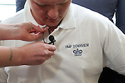 A student fitting a radio microphone to one of the prison guards at HMP Downview during a media training session.