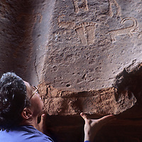 A traveler studies ancient petroglyphs carved into a cliff in Jordan's Wadi Rum.