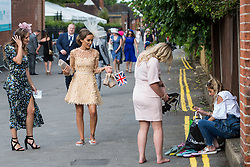 Ascot, UK. 20 June, 2019. Racegoers replace high heels with flipflops as they leave Royal Ascot after attending Ladies Day.
