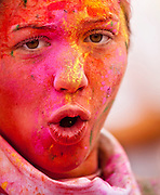 """A young woman is bathed in colorful dyes after finishing a charity footrace - a speck of  yellow powdered dye falls from her nose. -- Determine pricing and license this image, simply by clicking """"Add To Cart"""" below --"""