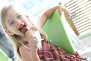 Young girl of three eats chocolate ice cream