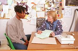 Teenage boy sitting at desk in office talking to female probation worker,