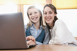 Portrait of schoolgirl and female childcare assistant with laptop