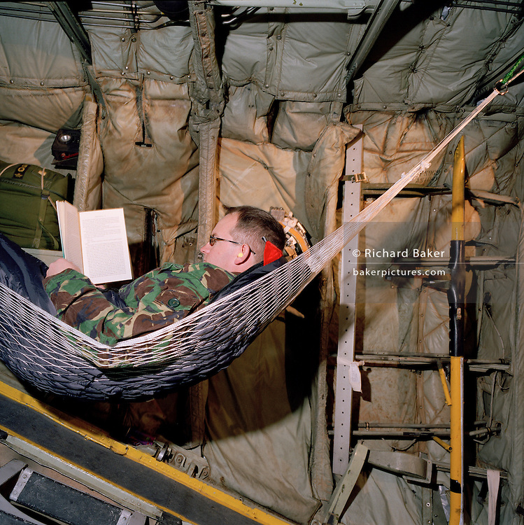 Corporal Chris Ward, one of the photographers belonging to the elite 'Red Arrows', Britain's prestigious Royal Air Force aerobatic team, reads a novel while wrapped up in sleeping bag and hammock aboard a C-130 Hercules transport aircraft during a two-day journey from RAF Scampton to RAF Akrotiri, Cyprus. Corporal Ward has established for himself a comfortable nest in the rear section at the loading ramp. The interior is basic with sharp corners but the walls are padded.  Ward wears a heavy camoulflaged coat to counteract the cold and ear-plugs from the droning engines. The Red Arrows pilots fly their Hawk jet aircraft to air shows but on long journeys requiring the support of ground crew borrow RAF transporters that fly behind the main airborne squadron shipping 10 tons of spares and personal effects for their six-week winter training stay. . .