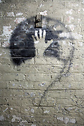 old paint peeling brick wall with spray painted question mark and hand imprint