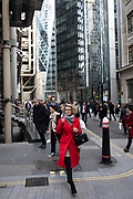 City worker in a red coat on her smart phone in the City of London on 28th January 2020 in London, England, United Kingdom. The City of London is a historic financial district, home to both the great banking buildings. Modern corporate skyscrapers tower above the vestiges of medieval alleyways below.