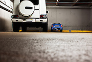 End-on view of a large SUV parked next to a tiny mini-car in a parking garage. WATERMARKS WILL NOT APPEAR ON PRINTS OR LICENSED IMAGES.