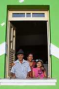 Brazilian Bahian family in bright green window; portrait showing three 3 generations, grandfather, daughter and her daughter, in Cachoeira.