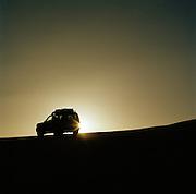 4x4 vehicle at sunset, Sahara Desert, Libya