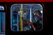 "A person wearing a protective face mask appears to be typing on his phone inside a double-deck red bus in Soho, London West End on early Monday, Sept 14, 2020. The public has been urged to act ""in tune"" with Covid-19 guidelines as the ""rule of six"" restrictions is into force on Monday. The British government's scientific advisory board announced on Friday that the reproduction number of coronavirus transmission across the UK was now over 1.0. The Science and the Scientific Advisory Group for Emergencies (SAGE) said the R-value was now between 1.0 and 1.2. (VXP Photo/ Vudi Xhymshiti)"