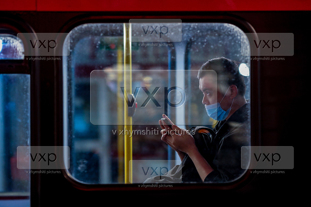 """A person wearing a protective face mask appears to be typing on his phone inside a double-deck red bus in Soho, London West End on early Monday, Sept 14, 2020. The public has been urged to act """"in tune"""" with Covid-19 guidelines as the """"rule of six"""" restrictions is into force on Monday. The British government's scientific advisory board announced on Friday that the reproduction number of coronavirus transmission across the UK was now over 1.0. The Science and the Scientific Advisory Group for Emergencies (SAGE) said the R-value was now between 1.0 and 1.2. (VXP Photo/ Vudi Xhymshiti)"""