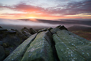 Colourful dawn skies from the gritstone boulders of Higger Tor. A layer of mist hangs over Burbage Brook and partially enshrouds Carl Wark (Iron Age Hill Fort) to the right side. Hathersage Moor, Peak District National Park, Derbyshire, England, UK. October. Autumn.