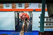 18 JUNE 2013 - YANGON, MYANMAR:   Stevedores unload a river freighter on the docks in Yangon, Myanmar.     PHOTO BY JACK KURTZ