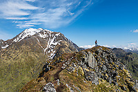 Female hiker on trail to Mannen with Himmeltindan in background, Vestvågøy, Lofoten Islands, Norway