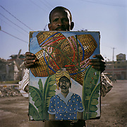 "Phillip Acheles, 47, Main Street, artist. Phillip is a self-taught artist. He was selling this and other artists'  paintings in down-town Port Au Prince, a sign that the economy is moving again, albeit in a limited capacity. ""Not since 2006 has there been any prosperity in this country,"" says Phillip. ""It has been in a state of political crisis  for years now. Every time there is  a small recovery, something happens and now the earthquake means the chance of selling paintings to tourists is once more very low."""