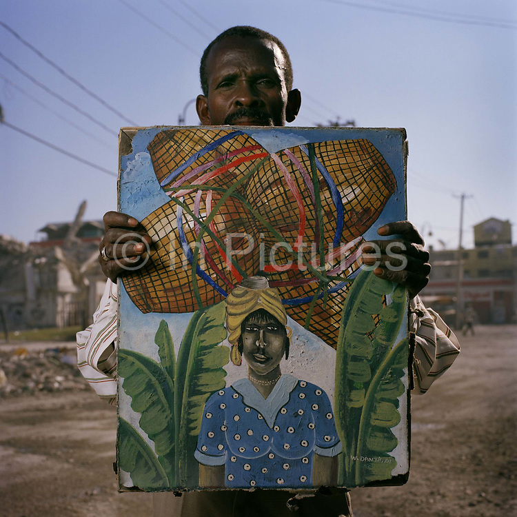 """Phillip Acheles, 47, Main Street, artist. Phillip is a self-taught artist. He was selling this and other artists'  paintings in down-town Port Au Prince, a sign that the economy is moving again, albeit in a limited capacity. """"Not since 2006 has there been any prosperity in this country,"""" says Phillip. """"It has been in a state of political crisis  for years now. Every time there is  a small recovery, something happens and now the earthquake means the chance of selling paintings to tourists is once more very low."""""""