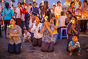 """29 JANUARY 2013 - PHNOM PENH, CAMBODIA:  A family prays for late Cambodian King Norodom Sihanouk on the plaza in front of the Royal Palace in Phnom Penh. Sihanouk (31 October 1922- 15 October 2012) was the King of Cambodia from 1941 to 1955 and again from 1993 to 2004. He was the effective ruler of Cambodia from 1953 to 1970. After his second abdication in 2004, he was given the honorific of """"The King-Father of Cambodia."""" Sihanouk held so many positions since 1941 that the Guinness Book of World Records identifies him as the politician who has served the world's greatest variety of political offices. These included two terms as king, two as sovereign prince, one as president, two as prime minister, as well as numerous positions as leader of various governments-in-exile. He served as puppet head of state for the Khmer Rouge government in 1975-1976. Most of these positions were only honorific, including the last position as constitutional king of Cambodia. Sihanouk's actual period of effective rule over Cambodia was from 9 November 1953, when Cambodia gained its independence from France, until 18 March 1970, when General Lon Nol and the National Assembly deposed him. Upon his final abdication, the Cambodian throne council appointed Norodom Sihamoni, one of Sihanouk's sons, as the new king. Sihanouk died in Beijing, China, where he was receiving medical care, on Oct. 15, 2012. His cremation is scheduled to take place on Feb. 4, 2013. Over a million people are expected to attend the service.      PHOTO BY JACK KURTZ"""