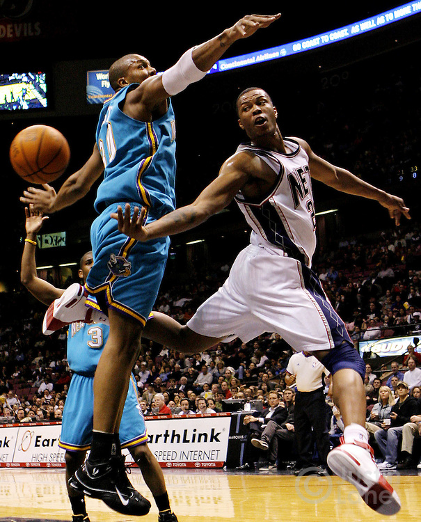 The Nets' Antoine Wright (R) passes past the Hornets' David West (L) during the second half of the New Orleans/Oklahoma City Hornets' 111-107 victory over the New Jersey Nets at Continental Airlines Arena in East Rutherford, New Jersey on Wednesday 21 February 2007.