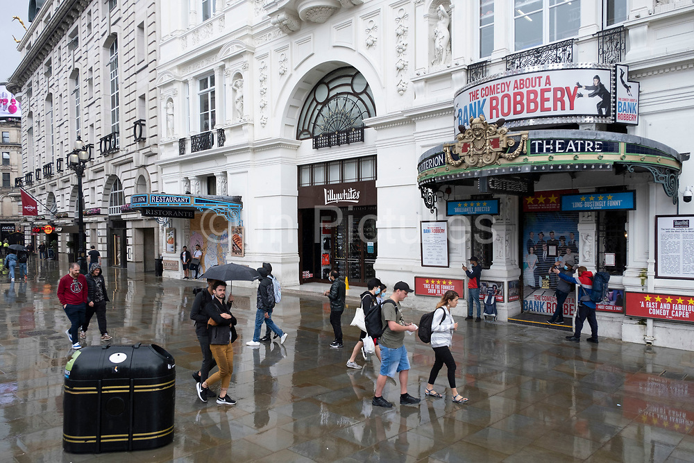 People sheltering from the rain outside the closed Criterion Theatre in a very quiet Piccadilly Circus during a rain shower under coronavirus lockdown on 1st July 2020 in London, England, United Kingdom. As the July deadline approaces and government will relax its lockdown rules further, the central London remains very quiet, while some non-essential shops are allowed to open with individual shops setting up social distancing systems.
