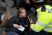 Glued on protesters has section 14 notice read to her by police before being arrested during Extinction Rebellion disruption outside City Airport on 10th October 2019 in London, England, United Kingdom. The protest is against the climate and pollution impact of the government's plans for airport expansion which will potentially double the amount of flights coming from City Airport. Extinction Rebellion is a climate change group started in 2018 and has gained a huge following of people committed to peaceful protests. These protests are highlighting that the government is not doing enough to avoid catastrophic climate change and to demand the government take radical action to save the planet.