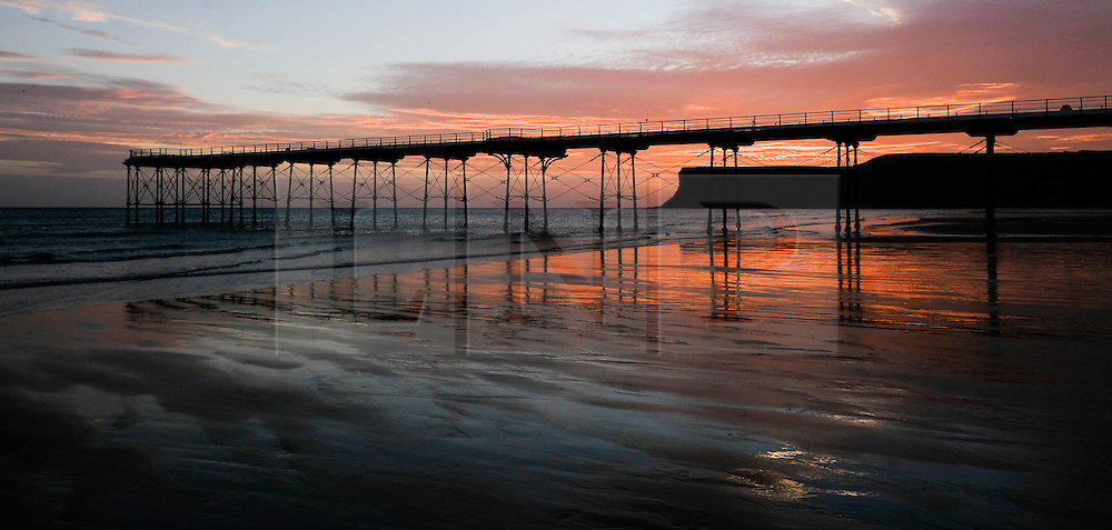 © Licensed to London News Pictures. <br /> 28/09/2016. <br /> Saltburn-by-the-Sea, UK.  <br /> <br /> Clouds over Saltburn by the Sea turn a dramatic orange as the sun begins to rise.<br /> <br /> Photo credit: Ian Forsyth/LNP