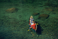 A young couple paddles a canoe in Grand Teton National Park, Jackson Hole, Wyoming.