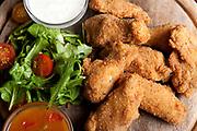 Deep fried breaded chicken wings on a wooden platter