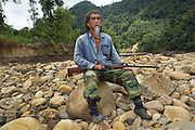 Kelabit man, Fredrick Ngareng, with gun on beach, twenty years later. Sedentary Dayaks, living in longhouses, they rely on fishing, hunting and farming to survive. Limbang, Sarawak, Malaysia 2015<br /> <br /> Borneo native peoples and their rainforest habitat revisited two decades later: 1989/1991 and 2012/2014/2015. <br /> <br /> Sarawak's primary rainforests have been systematically logged over decades, threatening the sustainable lifestyle of its indigenous peoples who relied on nomadic hunter-gathering and rotational slash & burn cultivation of small areas of forest to survive. Now only a few areas of pristine rainforest remain; for the Dayaks and Penan this spells disaster, a rapidly disappearing way of life, forced re-settlement, many becoming wage-slaves. Large and medium size tree trunks have been sawn down and dragged out by bulldozers, leaving destruction in their midst, and for the most part a primary rainforest ecosystem beyond repair. Nowadays palm oil plantations and hydro-electric dam projects cover hundreds of thousands of hectares of what was the world's oldest rainforest ecosystem which had some of the highest rates of flora and fauna endemism, species found there and nowhere else on Earth, and this deforestation has done irreparable ecological damage to that region