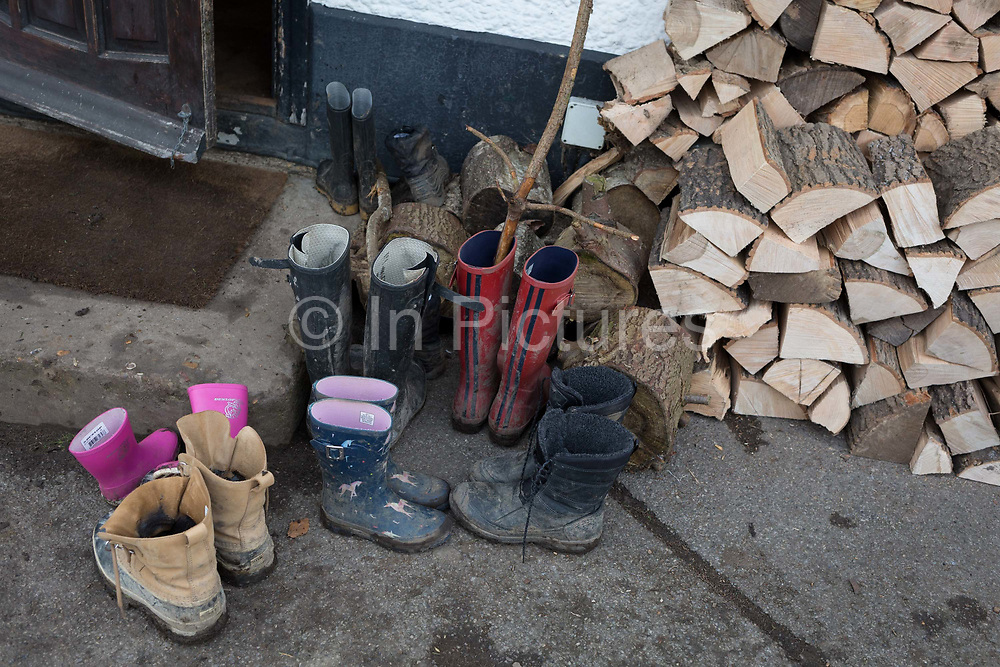 A woodland walker leaves his muddy boots next to a pile of other outdoor walkers boots which have been left outside the Bucks Head pub in Godden Green, on 5th January 2019, in Kent, England.